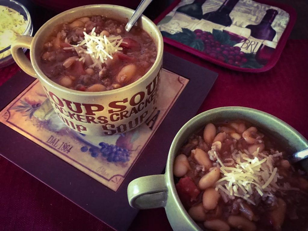 Italian Chili in serving bowls. Italian Chili made with Italian hot sausage, Italian mild sausage, Cannellini white kidney beans, dry red wine, fire roasted diced tomatoes, diced white or yellow onion, chopped garlic cloves, tomato paste, chicken broth, crushed red pepper, sea salt, and pepper.