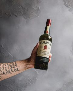 A tattooed man's arm holding out a green bottle of Jameson Irish whiskey against a grey wall.