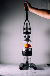 A silver hand juice press squeezing an orange to make fresh orange juice.