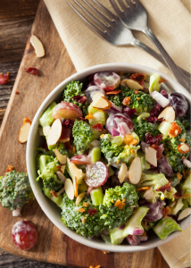 A creamy crunchy broccoli salad made with broccoli florets, crumbled bacon, chopped red onion, shredded cheddar cheese, cashews, grapes, craisins, mayo, white vinegar, & sugar.